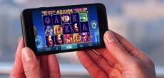 Händer håller mobil med slots